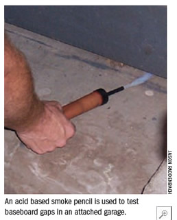 An acid based smoke pencil is used to test baseboard gaps in an attached garage.